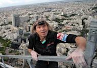 """French """"Spiderman"""" Alain Robert, pictured here climbing Paris' First Tower in May, added another structure to his record of climbing achievements on Saturday, scaling most of a 388-metre (1,280-foot) tower in central China"""
