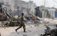 A policeman walks at the scene of an explosion near the entrance of the airport in Somalia's capital Mogadishu February 13, 2014. REUTERS/Feisal Omar
