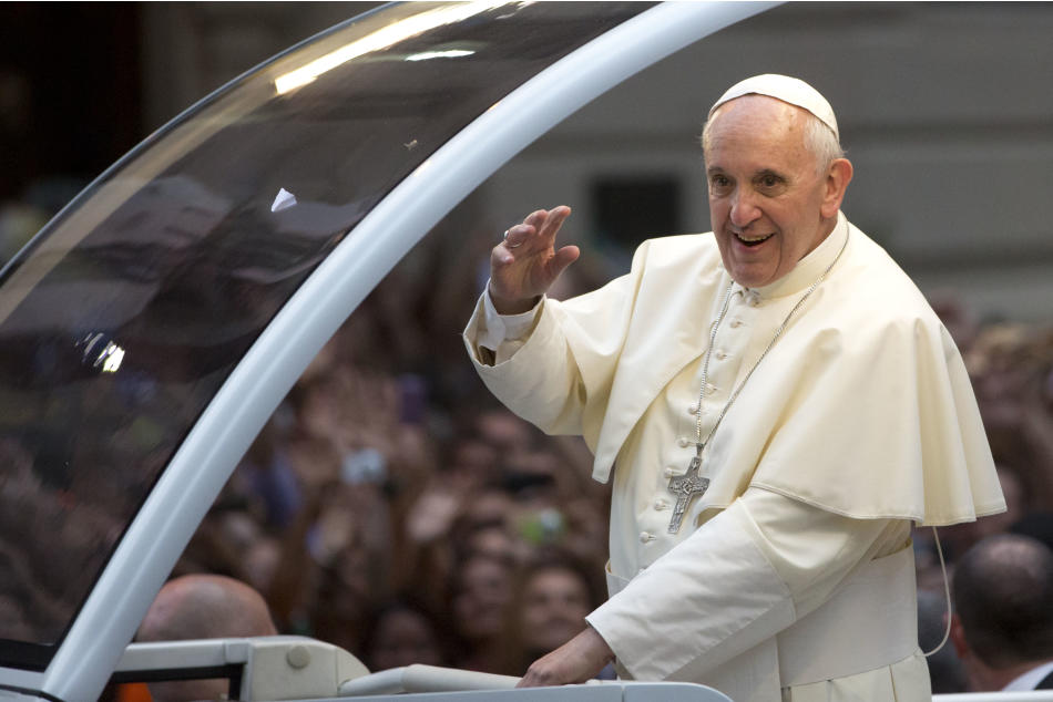 Pope Francis waves from his popemobile as he makes his way into central Rio de Janeiro, Brazil, Monday, July 22, 2013. The pontiff arrived for a seven-day visit in Brazil, the world's most populous Ro
