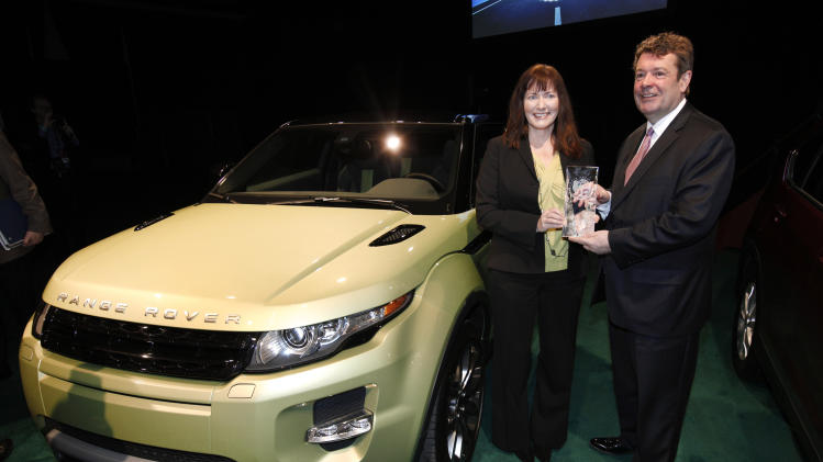 Kim McCullough, Brand Vice President, and Andy Goss, President, Land Rover North America, hold the North American Truck  of the Year trophy for the Land Rover Range Rover Evoque at the North American International Auto Show in Detroit, Monday, Jan. 9, 2012. (AP Photo/Paul Sancya)