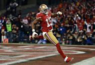 SAN FRANCISCO, CA - JANUARY 12: Wide receiver Michael Crabtree #15 of the San Francisco 49ers runs the ball in for a touchdown thrown by quarterback Colin Kaepernick #7 in the second quarter against the Green Bay Packers during the NFC Divisional Playoff Game at Candlestick Park on January 12, 2013 in San Francisco, California. (Photo by Harry How/Getty Images)