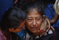 A relative of one of the Nepalese climbers killed in an avalanche on Mount Everest, cries during the funeral ceremony in Katmandu, Nepal, Monday, April 21, 2014. Buddhist monks cremated the remains of Sherpa guides who were buried in the deadliest avalanche ever recorded on Mount Everest, a disaster that has prompted calls for a climbing boycott by Nepal's ethnic Sherpa community. The avalanche killed at least 13 Sherpas. Three other Sherpas remain missing and are presumed dead. (AP Photo/Niranjan Shrestha)