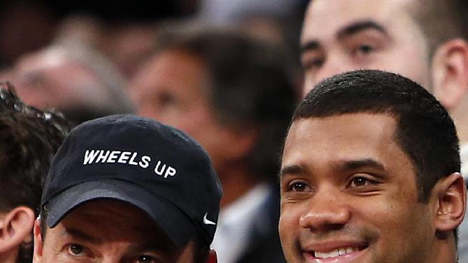 CORRECTS NAME OF MAN AT LEFT TO KENNY DICHTER, CEO OF WHEELS UP, INSTEAD OF ACTOR STEVE SCHIRRIPA - Kenny Dichter, CEO of Wheels Up, left, and Seattle Seahawks quarterback Russell Wilson pose for a photograph together as they attend an NBA basketball game between the Dallas Mavericks and the New York Knicks, Monday, Feb. 24, 2014, in New York. Dallas won 110-108