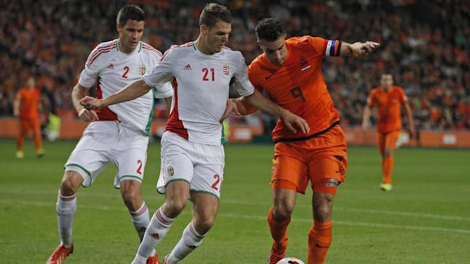Netherlands' Robin van Persie, right, and Hungary's Zsolt Korcsmar, second left, and Hungary's Richard Guzmics, left, vie for the ball during the Group D World Cup qualifying soccer match between Netherlands and Hungary, at ArenA stadium in Amsterdam, Netherlands, Friday Oct. 11, 2013. The Netherlands won the match with a 8-1 score