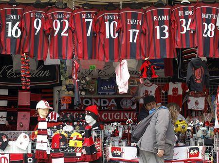 A woman looks at AC Milan merchandise outside the San Siro stadium in Milan
