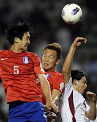 South Korea's Kwak Tae Hwi (L) heads the ball to score against Qatar during their group B 2014 World Cup Asian qualifying football match in Doha. South Korea won 4-1