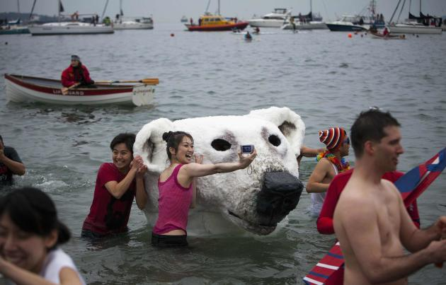 People pose next to a polar bear costume worn by two participants in English Bay during the 94th annual New Year's Day Polar Bear Swim in Vancouver