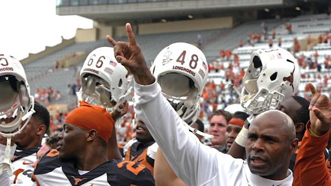 """Texas coach Charlie Strong gives the """"hook 'em horns"""" sign while his players raise their helmets after the Orange and White spring NCAA college football game, Saturday, April 19, 2014, in Austin, Texas"""