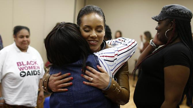 "Grammy Award-winning singer Alicia Keys hugs HIV positive woman as she visits an HIV women's support group at United Medical Center in Washington, Monday, April 15, 2013. Keys is working with the Kaiser Family Foundation for ""Empowered,"" a campaign launched last month to educate women about HIV/AIDS and provide grants to community based projects that will do that. (AP Photo/Charles Dharapak)"