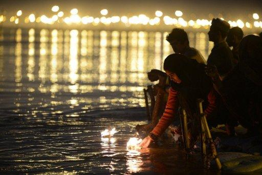 A woman devotee releases an offering into the water for the Maha Kumbh Mela, in Allahabad, on February 9, 2013