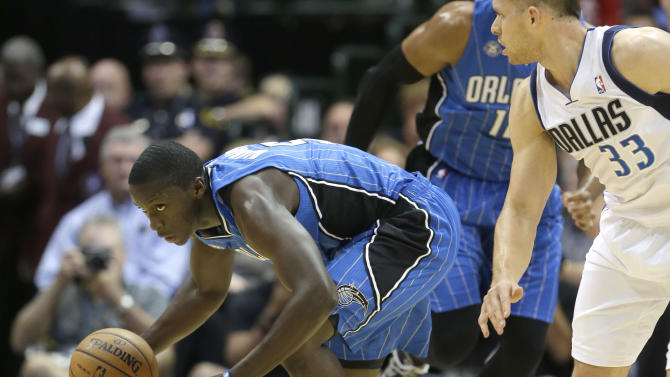 Orlando Magic shooting guard Victor Oladipo (5) steals the ball from Dallas Mavericks point guard Gal Mekel (33)  during the first half of an NBA preseason basketball game in Dallas,  Monday, Oct. 14, 2013.  The Magic won 102-94