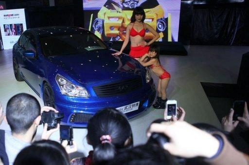 This photo taken on November 16 shows a young child (C) and a model posing beside a car during the Chutian Auto Culture Festival in Wuhan. The company that featured bikini-clad child models as young as five years old at a Chinese car show sought Wednesday to defuse the controversy but also defended its actions