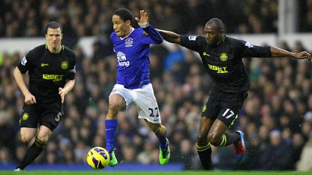Everton's Steven Pienaar (centre) Wigan Athletic's Emmerson Boyce (right) battle for the ball