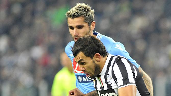 Juventus forward Carlos Tevez, of Argentina, challenges for  the ball with Napoli's Valon Berhami, during a Serie A soccer match between Juventus and Napoli at the Juventus stadium, in Turin, Italy, Sunday, Nov, 10, 2013