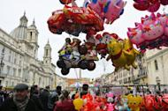 """Shoppers walk in Piazza Navona in Rome in 2011. Italy on Wednesday said its recession would deepen in 2012 with the economy shrinking 1.2 percent and delayed a target to balance its budget by 2013, warning there was still """"a long way to go."""""""