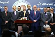 Iraqi Deputy Prime Minister Saleh al-Mutlaq (2L) and former parliament speaker Osama al-Nujaifi (3R) listen on as Sunni Muslim MP Dhafer al-Aanie (C) give a press conference after the new parliament failed to elect a speaker on July 1, 2014