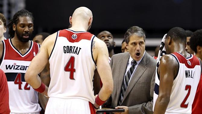 Washington Wizards head coach Randy Wittman, second from right, talks with his team, including forward Nene (42), from Brazil, center Marcin Gortat (4), from Poland, and guard John Wall (2) during a timeout in the second period of an NBA basketball game against the Cleveland Cavaliers, Saturday, Nov. 16, 2013, in Washington. The Cavaliers won 103-96 in overtime