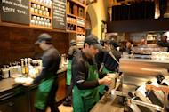 Staff work behind the counter of India's first newly-inaugurated Starbucks outlet in Mumbai on October 19, 2012