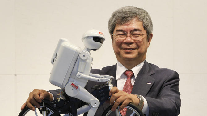 "Murata President Murata poses with his company's bicycle-riding robot ""Murata Seisaku-kun"" after an interview in Chiba"