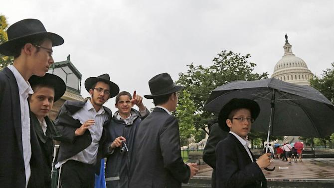 Students from Oholei Torah school in Crown Heights, Brooklyn arrive in a drizzle to visit the U.S. Capitol in Washington, Thursday, June 13, 2013. Massive thunderstorms that swept through the Midwest are pushing toward the Mid-Atlantic states. Meteorologists warn that the line of storms could launch a weather event called a derecho, which is a straight-line wind storm spanning at least 240 miles. (AP Photo/Charles Dharapak)