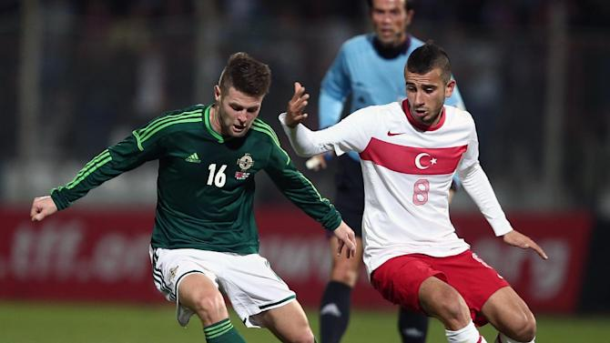 Turkey's Oguzhan Ozyakup, right, and Oliver Norwood of Northern Ireland fight for the ball during their friendly soccer match in Adana, Turkey, Friday, Nov. 15, 2013. (AP Photo)