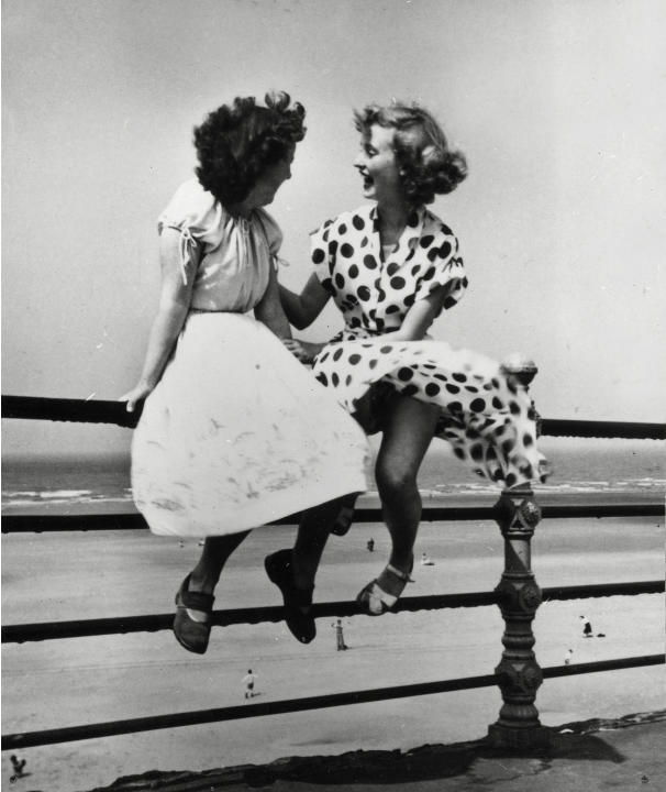 Two young women sit on a railing in Blackpool in 'Maidens in Waiting', 1951. This is one of Hardy's most recognisable images and captures a carefree post-War Britain (Bert Hardy/ Getty Ima