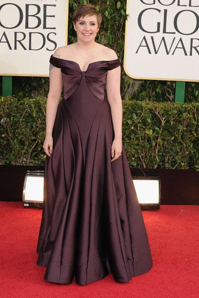 Lena Dunham: It's a miracle! 'Girls' star Lena Dunham is wearing a full-on gown! The plum-coloured frock is super flattering on the writer/director/actor and works well with her cute pixie cut. (Photo by Steve Granitz/WireImage)