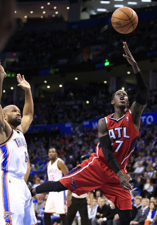 Atlanta Hawks guard Dennis Schroder, right, goes to the basket in front of Oklahoma City Thunder guard Derek Fisher, left, during the second quarter of an NBA basketball game Monday, Jan. 27, 2014, in Oklahoma City