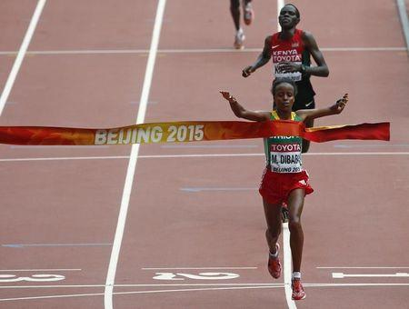 Dibaba crosses the finish line first to win the women's marathon at the 15th IAAF Championships in Beijing