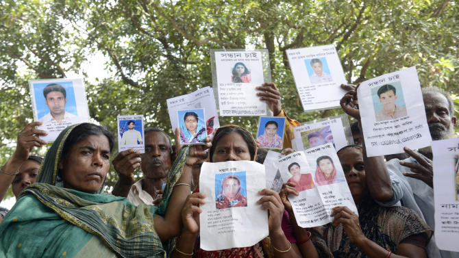 Relatives hold up portraits of many still missing from last week's collapse of a garment factory building, Thursday, May 2, 2013, in Savar, near Dhaka, Bangladesh. Rescuers found more bodies in the concrete debris of the collapsed garment factory building Thursday and authorities said it may take another five days to clear the rubble. In addition to the 430 confirmed dead, police report another 149 people are still missing in what has become the worst disaster for Bangladesh's $20 billion-a-year garment industry that supplies global retailers.  (AP Photo/Ismail Ferdous)