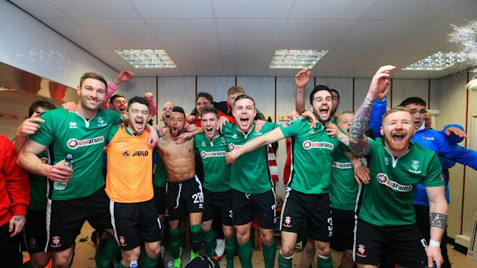 Lincoln City team celebrate their win in the changing room after The Emirates FA Cup Fifth Round match between Burnley and Lincoln City at Turf Moor