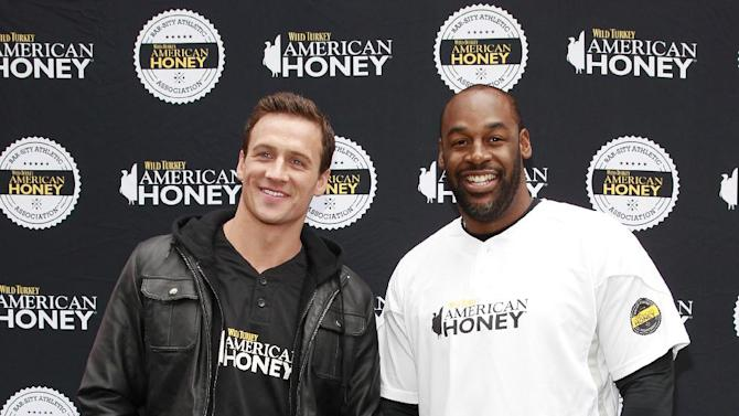 IMAGE DISTRIBUTED FOR AMERICAN HONEY - Eleven time Olympic medalist and TV start Ryan Lochte, left, and pro football legend Donovan McNabb host the first ever American Honey Bar-sity Athletics kickball game in Times Square, on Tuesday, April, 23, 2013 in New York City, New York. (Photo by Mark Von Holden/Invision for American Honey/AP Images)