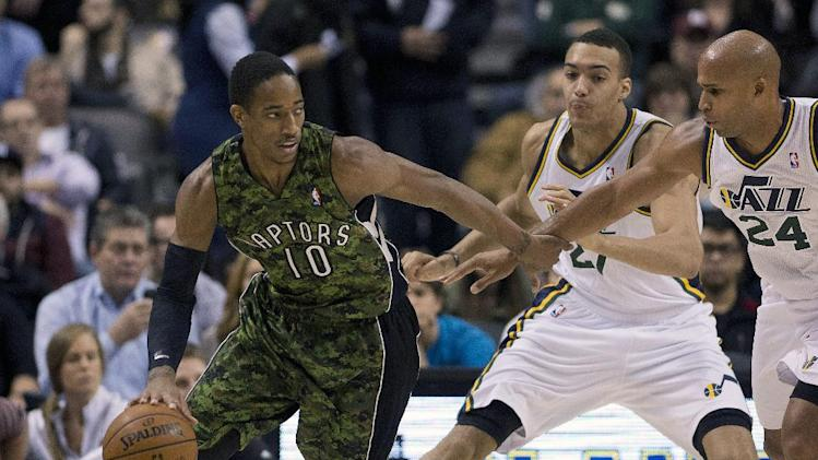 Toronto Raptors guard DeMar DeRozan (10) is defended by Utah Jazz forward Richard Jefferson (24) and centre Rudy Gobert (27) during the first half of an NBA basketball game in Toronto on Saturday, Nov. 9, 2013