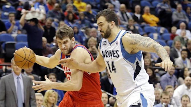 Philadelphia 76ers center Spencer Hawes, left, drives against Minnesota Timberwolves center Nikola Pekovic (14), of Montenegro, during the first quarter of an NBA basketball game in Minneapolis, Wednesday, Dec. 11, 2013