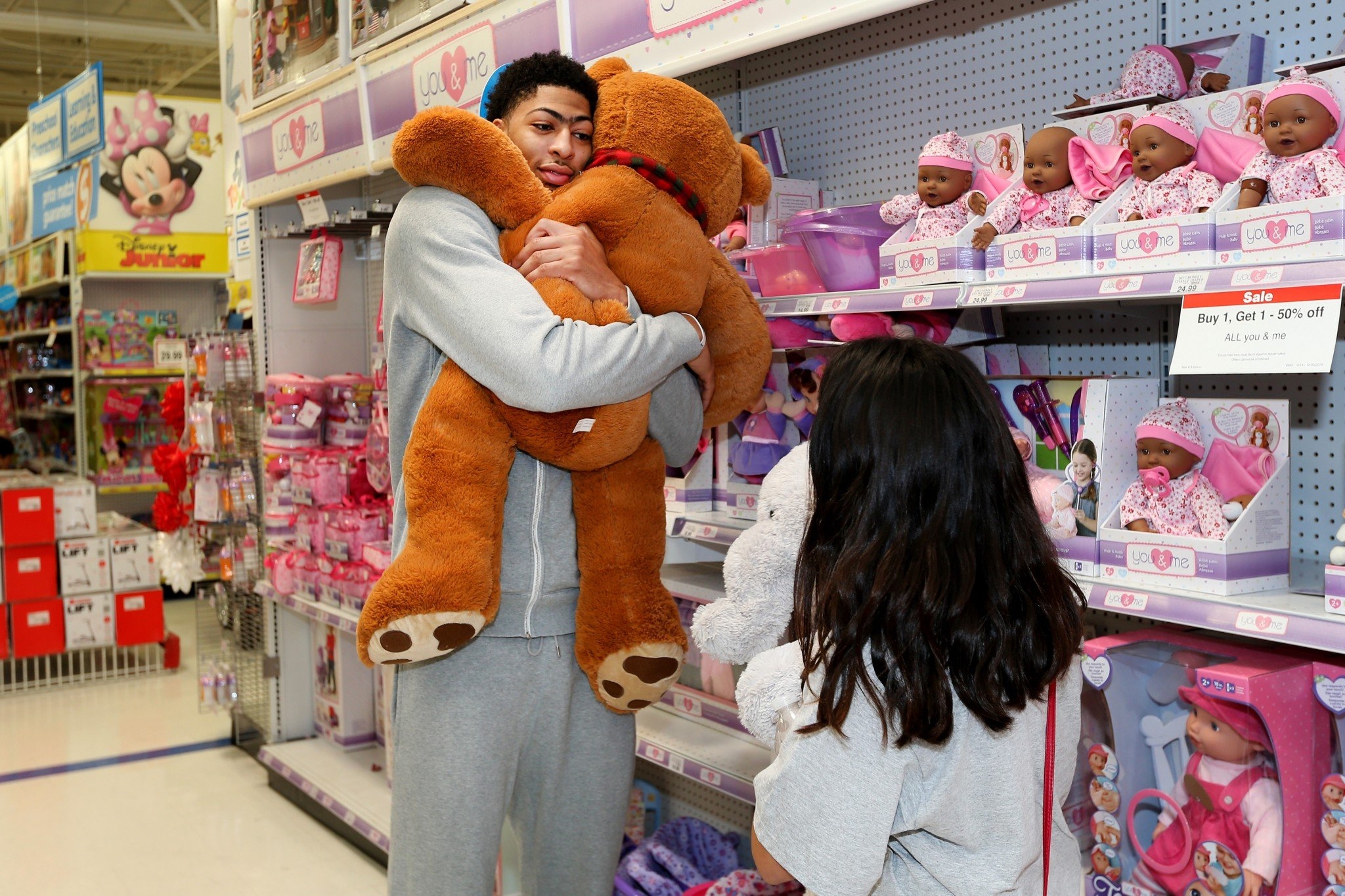 Anthony Davis embraces the holiday spirit, and a very large teddy bear, during a New Orleans Pelicans Shopping Spree event. (Getty Images)