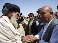 An Afghan government delegate (R) shakes hands with an elder at a mosque in Alokozai village of Pajwayi district in Kandahar province on March 13, 2012. Gunmen on Tuesday attacked an Afghan memorial service in Alokozai for 16 villagers killed by a US soldier, shooting dead a member of the Afghan military and wounding a policeman in a hail of gunfire