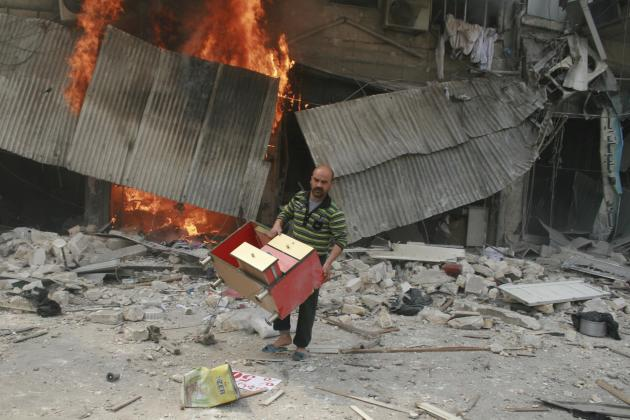 Man carries furniture out of a fire after what activists said was an air strike by forces loyal to Syrian President Assad in Aleppo's Bustan al-Qasr