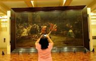 """A tourist takes a photograph of the restored painting """"Spoliarium"""", at the National Museum in Manila in June 2011. Flash camera-toting tourists could wreck the Philippines' greatest work of art, say the worried curator of the """"Spoliarium"""", a symbol of Filipino awakening against Spain's colonial yoke"""