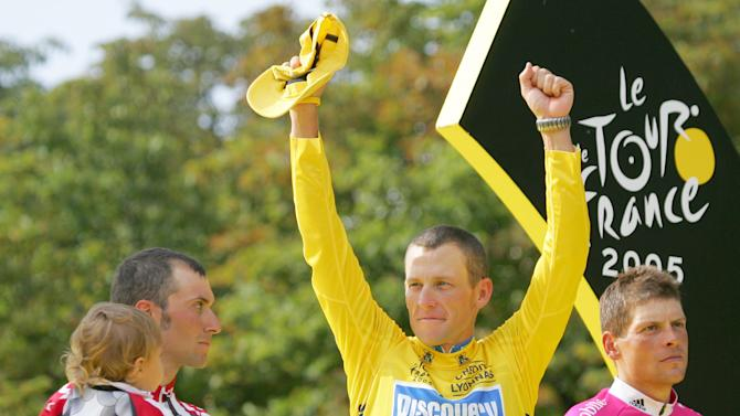 In this July 24, 2005 file photo,  Lance Armstrong gestures from the podium after winning his seventh straight Tour de France cycling race, as second-placed Ivan Basso of Italy, left, and third-placed Jan Ullrich of Germany, look on, after the 21st and final stage of the race in Paris. Armstrong, he superstar cyclist whose stirring victories after his comeback from cancer helped him transcend sports, chose not to pursue arbitration in the drug case brought against him by the U.S. Anti-Doping Agency. That was his last option in his bitter fight with USADA and his decision set the stage for the titles to be stripped and his name to be all but wiped from the record books of the sport he once ruled.  (AP Photo/Christophe Ena, File)