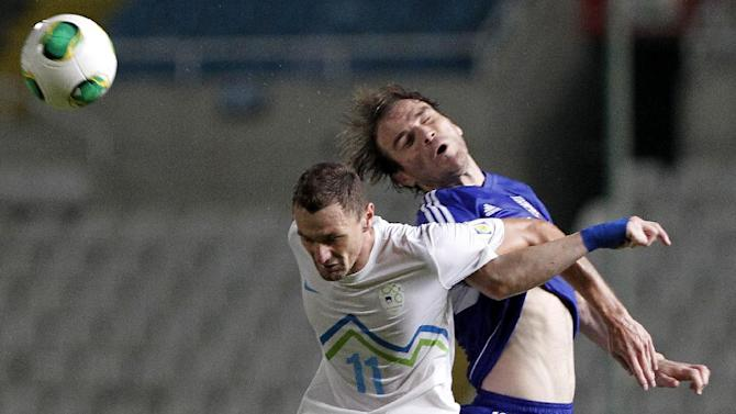 Cyprus' Sinisa Dobrasinovic, right, jumps for the ball with Slovenia's Milivoje Novakovic during their World Cup group E qualifying soccer match at GSP stadium in Nicosia, Cyprus, Tuesday, Sept. 10, 2013