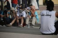 A Bahraini Shiite Muslim man wears a T-shirt calling for the downfall of the king sat a protest following the funeral of Ahmad Ismail Hassan on Friday. Several people were wounded during the funeral ceremony, says Al-Wefaq, the main Shiite opposition movement in the Sunni-ruled nation with a Shiite-majority population