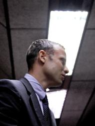 South Africa's Olympic sprinter Oscar Pistorius leaves the courtroom at the the Magistrate Court in Pretoria after his hearing on the charge of murdering his girlfriend Reeva Steenkamp on Valentine's Day, on February 15, 2013. The double amputee, an inspirational hero of last year's London Olympics, sat hunched as the court heard that prosecutors would argue that the murder was premeditated