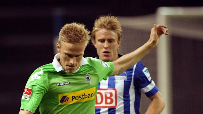 Moenchengladbach's Oscar Wendt, left, andBerlin's Per Skjelbred challenge for the ball during the German first division Bundesliga soccer match between Hertha BSC Berlin and Borussia Moenchengladbach, in Berlin, Germany, Saturday, Oct. 19, 2013