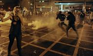 Protestors clash with riot squad officers on a street near Maracana stadium in Rio de Janeiro, Brazil on June 30, 2013. Protesters complain the government has found billions of dollars to build brand new stadiums for 12 World Cup host stadiums while transport, education and health remain underfunded