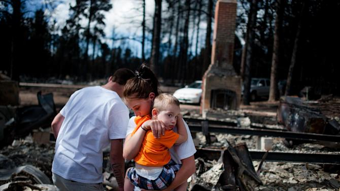 Brandy Burton carries her son Caiyleb Lewis, 2, through the rubble of her family's home that was completely destroyed in the Black Forest Fire, Tuesday, June 18, 2013, in Colorado Springs, Colo. Residents were allowed back into the area for a short period of time to view the properties that sustained the most damage from the fire. The Black Forest Fire, the most destructive wildfire in Colorado history, has destroyed 502 homes and charred more than 22 square miles. It was 85 percent contained Tuesday. (AP Photo/The Colorado Springs Gazette, Michael Ciaglo) MAGS OUT