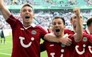 (From left) Hanover's Polish striker Artur Sobiech, midfielder Szabolcs Huszti and Konstantin Rausch celebrate after scoring during the German first division Bundesliga match against Wolfsburg in Wolfsburg. Ten-man Wolfsburg suffered their worst Bundesliga home defeat this century after they were routed 4-0 by Hanover 96