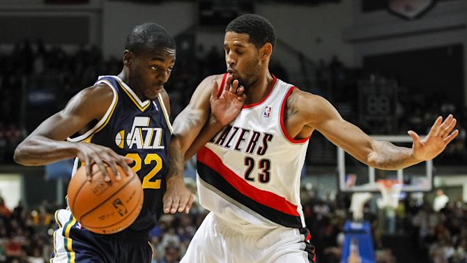 Utah Jazz shooting guard Justin Holiday (22) protects the ball from Portland Trail Blazers shooting guard Allen Crabbe (23) in the first half of a preseason NBA basketball game on Friday, Oct. 11, 2013, in Boise, Idaho. Portland won 96-86