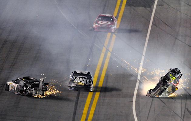 Jeff Gordon's car, right, rolls after a collision with Kurt Busch, left, as Jimmie Johnson, center, drives past in his damaged car during the NASCAR Budweiser Shootout auto race at Daytona Internation