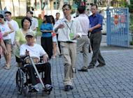 A presiding officer leads a voter in a wheelchair to a polling centre in Singapore. Singapore's ruling People's Action Party (PAP) was returned to power on Sunday with a huge majority but lost a key district to the opposition, costing a senior cabinet minister his job