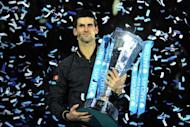 Serbia's Novak Djokovic poses with the winners' trophy after the singles final against Switzerland's Roger Federer on the eighth day of the ATP World Tour Finals tennis tournament in London